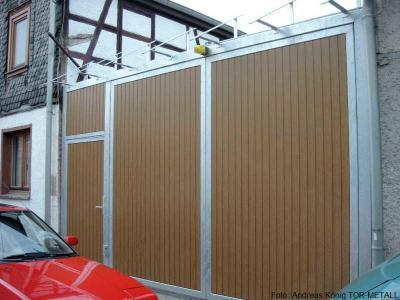 Kraftbetätigte 2-flgl. Drehtoranlage mit Nebeneingangstür mit Oberlicht und Vordachunterkonstruktion Fabr. Andreas König TOR-METALL